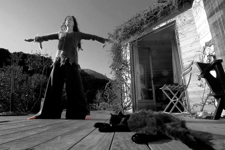 jeune femme devant une cabane les bras ouverts