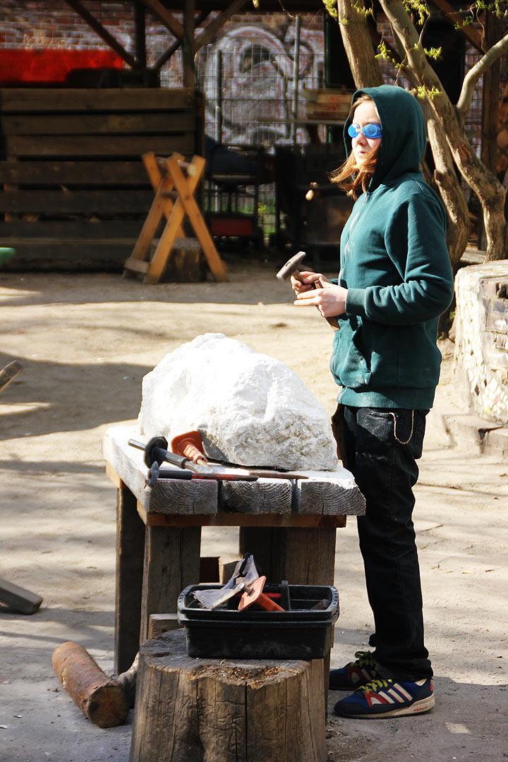 adolescent travaillant la pierre avec des burins